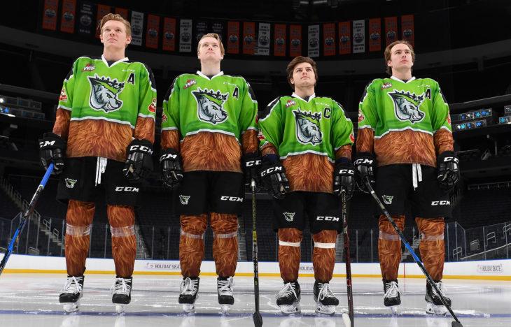 Wyatt McLeod (6), Conner McDonald (37), Trey Fix-Wolansky (27) and Ethan Cap (8) show off the Edmonton Oil Kings 2018-19 Teddy Bear Toss jerseys at Rogers Place.