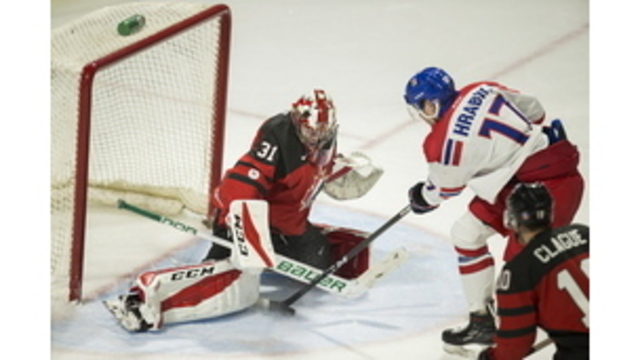 Czech Republic's Krystof Hrabik tries to put the puck past Canada goalie Carter Hart during the third period of a World Junior Championships exhibition hockey game in London, Ontario, Wednesday, Dec. 20, 2017. (Geoff Robins/The Canadian Press via AP)